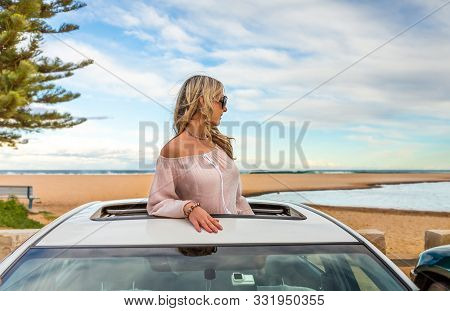 Rolad Trip Summer Beach Vibes.  Woman Stand In The Sunroof Of Her Car By The Beach.  Travel, Transpo