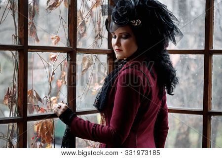 Portrait Of A Nice Young Adult Woman Wearing Old-fashioned Vampire-style Clothes At The Window Of Th