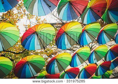 Gay Rainbow Colored Umbrellas. Walking Under Rainbow Umbrellas In Gay Parade. Gay People. Gay Rainbo
