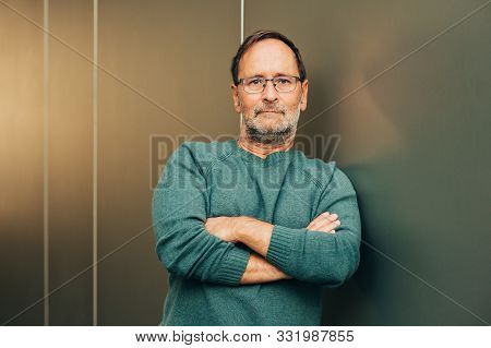 Outdoor Portrait Of 50 - 55 Year Old Man Wearing Green Pullover And Eyeglasses, Arms Crossed