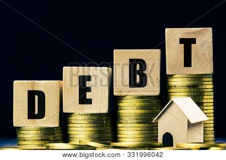 Conceptual About Property Debt. A Small House Model With Rising Stack Of Coins On Dark Background. D