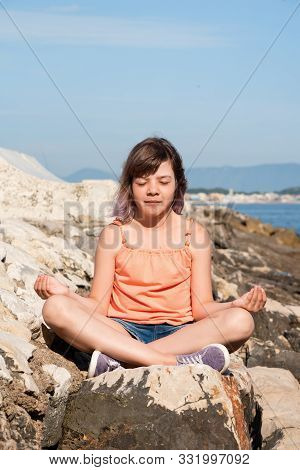 Teen Girl Is Sitting In Lotus Position On The Stone At Coast Of Sea