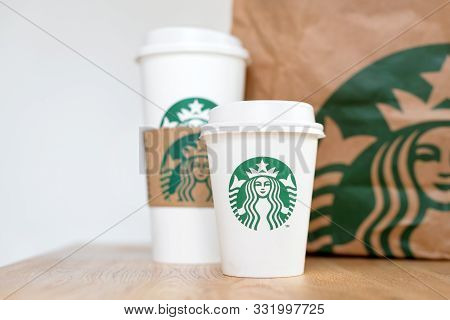 Kiev, Ukraine: November 06, 2019: Starbucks Coffee Take Away Cups With Paper Bag On Wooden Counter T