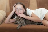 portrait of the girl with a cat on a sofa poster
