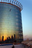 Rock climber hanging on rope attached to roof of high building at sunset poster