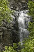 Waterfall against Rocks and Green Vegetation in Spearfish Canyon South Dakota. poster