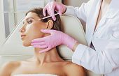 botulinum toxin injections in forehead. Anti aging procedure after 30 years, cosmetologist making injection poster