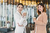 Two asian businesswomen talking during coffee break in modern office or coworking space, coffee break, relaxing and talking after working time, business and people partnership concept poster