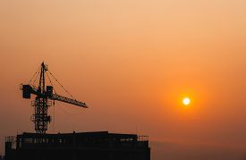 Crane Building Construction Site At Sunset Or Sunrise. High-quality Stock Photo Image Silhouette Of