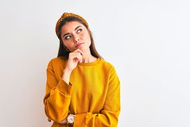 Young beautiful woman wearing yellow sweater and diadem over isolated white background with hand on chin thinking about question, pensive expression. Smiling with thoughtful face. Doubt concept.