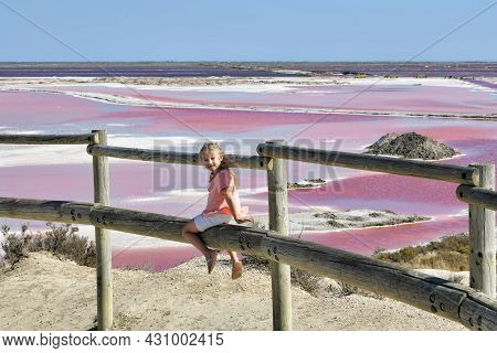 A Girl At The Salin-de-giraud Salt Farm With Pink Salty Water