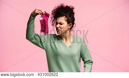Woman Feeling Disgusted While Holding Smelly Socks Isolated On Pink