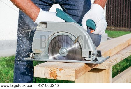 Working With A Power Tools. A Builder Is Sawing A Board At The Construction Site Of A New House. Clo