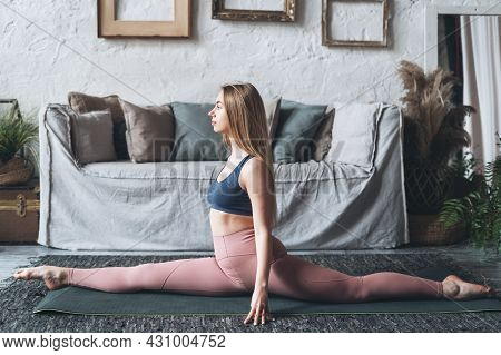 Young Slender Woman In Activewear Stretching Her Legs While Practicing Twine On Floor In Living Room