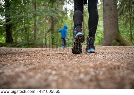 Low Angle View Of A Woman In Hiking Boots Walking On A Trail.