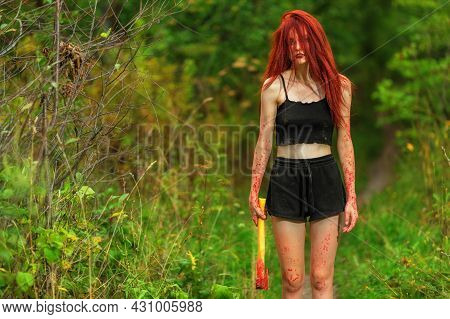 Red-haired Girl With Bloody Axe At Path In Summer Forest