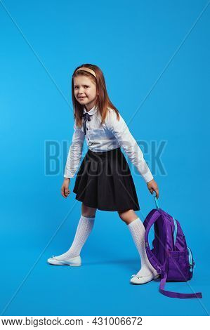 Vertical Photo Of Unhappy Schoolgirl In Uniform Holding A Heavy Backpack, Isolated Against Blue Back