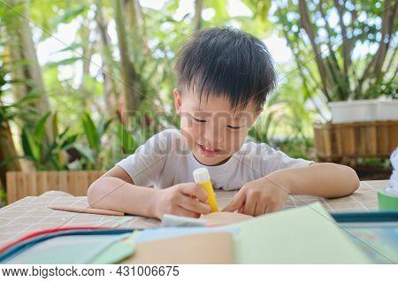 Cute Happy Smiling Asian Kindergarten Kid Enjoy Using Glue Doing Arts At Home, Fun Paper And Glue Cr