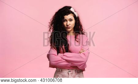 Displeased And Strict Woman Standing With Crossed Arms Isolated On Pink