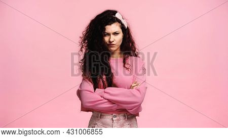 Angry Woman Grimacing While Standing With Crossed Arms Isolated On Pink