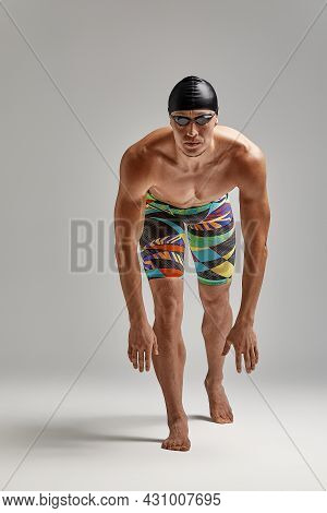 A Swimmer In Swimming Trunks Prepares For The Start, An Athlete On A Gray Background Prepares For A