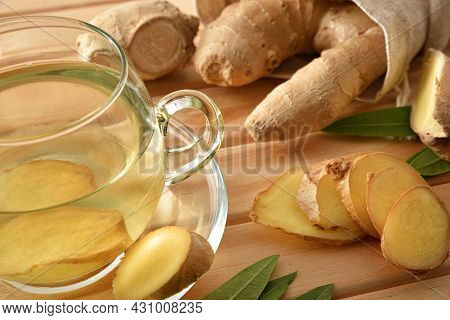 Organic Ginger Infusions On Wooden Table With Sliced Ginger Root And Sack Full Of Fresh Ginger Root.