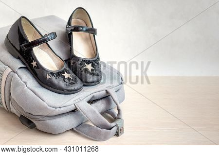 Close Up Of Black Old Worn School Shoes Near Briefcase On Light Background. Concept Of Expensive Sch