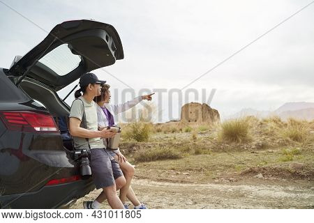 Asian Couple Leaning Against Back Of Car Looking At View While Drinking Coffee At Desolate Historica