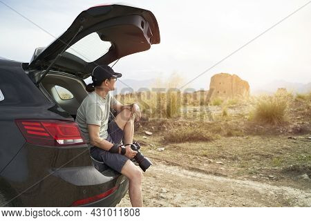 Asian Photographer Sitting At The Edge Of Trunk Of A Car Looking At A Deserted Castle With Camera In