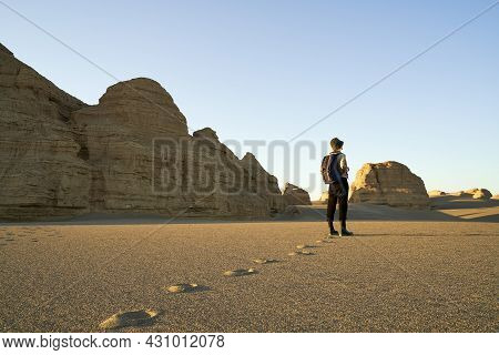 Asian Woman Traveler With Backpack Standing In Desert Looking At The Yardang Landform.