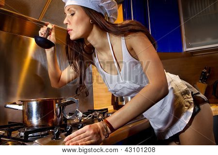 Portrait of sexy housewife chained by handcuffs to a pan. She tasting dish in kitchen room