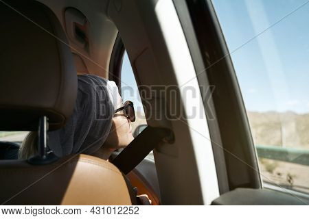 Asian Female Traveler Looking At View While Traveling By Car