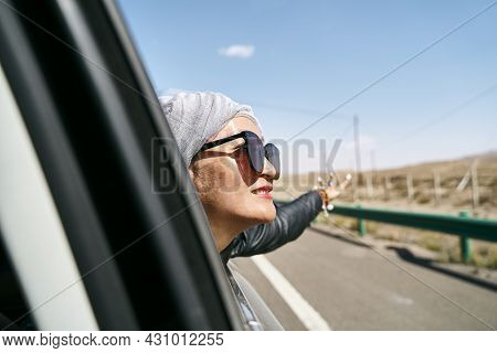 Asian Woman Tourist Sticking Head Out Of Rear Window Of A Car And Enjoying A Road Trip