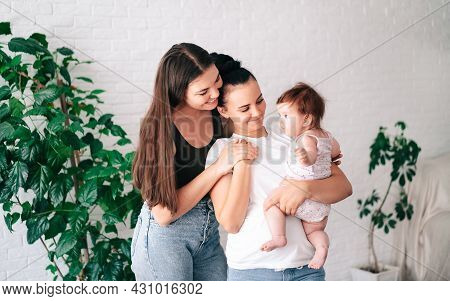 Two Beautiful Young Women In Casual Clothes Hug And Look At Their Little Child In The Apartment. The