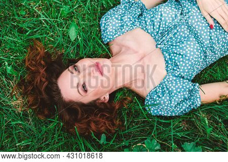 Beautiful Young Woman Lies On Green Grass With Loose Red Hair. The Woman Looks Up Dreamily. Beautifu
