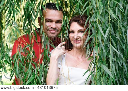 Portrait Of A Couple In Love In The Willow Branches. A Middle Eastern Man In A Red T-shirt With His
