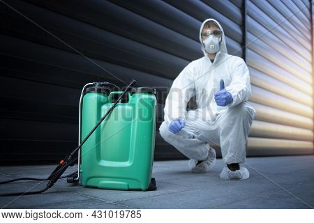 Exterminator In White Protective Uniform Standing By Reservoir With Chemicals And Sprayer.