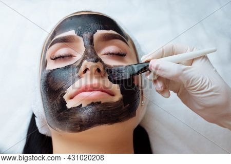 Cosmetologist Applying Black Mask On Pretty Woman Face Wearing Black Gloves, Gorgeous Woman In Spa H