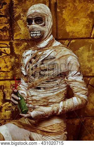 Scary Halloween mummy drinks soda standing by the wall with ancient Egyptian hieroglyphs. Halloween. Ancient Egyptian mythology.