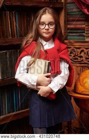Portrait of a cute modern girl in elegant classic school uniform posing in a luxurious vintage library interior. Kid's school fashion.