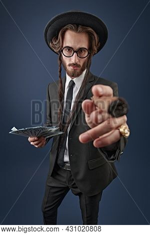 Portrait of a wealthy Jewish man with a gold ring on his finger and a bundle of banknotes, who smokes a cigar. Rich Jew concept.  Studio shot on a dark blue background.