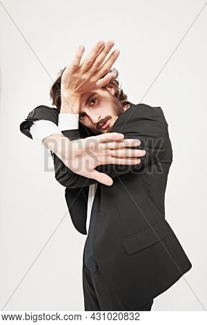 Fashion concept. Portrait of a handsome well-groomed man fashion model posing in motion at studio. White background.