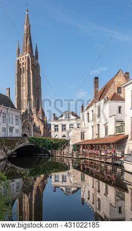 Brugge, Flanders, Belgium - August 4, 2021: Sunlit Onze Lieve Vrouw Cathedral Tower Under Blue Sky.