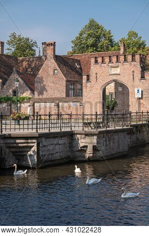 Brugge, Flanders, Belgium - August 4, 2021: Sunlit Red Brick Back Entrance To Housing Area Within Be