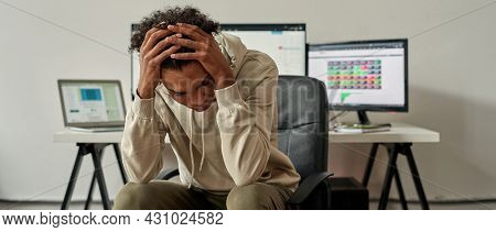 Frustrated Young Guy, Trader Holding Head, Feeling Depressed About Debt After Stock Market Business