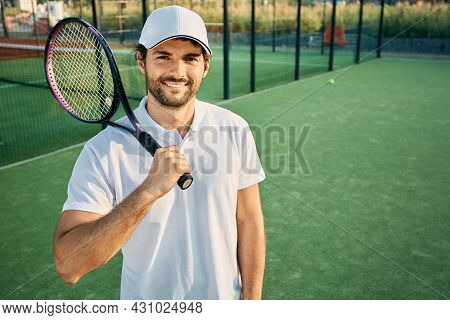 Portrait Of A Handsome Tennis Player With A Racket In Hand Standing On A Tennis Court Wearing A Whit