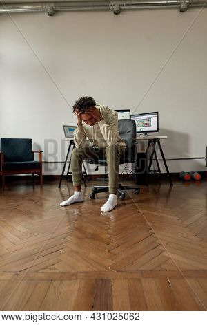 Frustrated Young Guy, Trader Holding Head In Panic After Stock Market Business Failure, Sitting At D