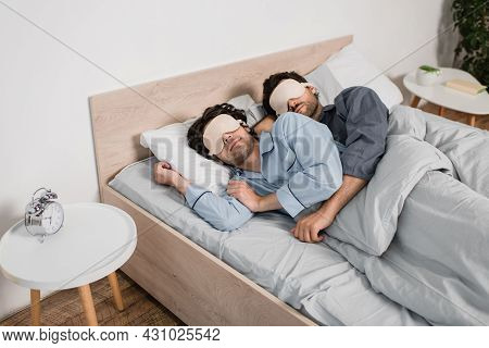 Gay Couple In Eye Masks Hugging While Sleeping In Bed