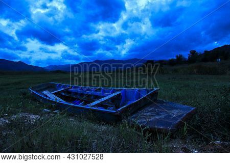 A Shipwreck Moored In The Middle Of A Field. In Front, A Large Mountain Was Visible And Rain Clouds