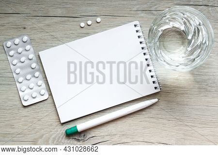 Medical Capsule Pills, Glass Water, Pen , Sheet Of Paper For Noteson Wooden Background. Concept Heal
